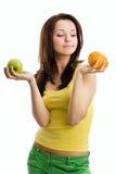 Mujer que elige entre la manzana anaranjada y verde Fotos de archivo libres de regalías