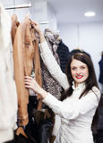 Mujer que elige la chaqueta en la tienda de ropa Imagen de archivo