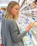 Mujer que elige la leche Fotografía de archivo libre de regalías