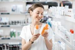 Mujer que elige la loción de la protección solar en la farmacia fotos de archivo