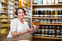 Mujer que elige la miel del surtido en droguería Fotografía de archivo
