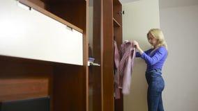 Mujer que elige la ropa delante del armario almacen de metraje de vídeo