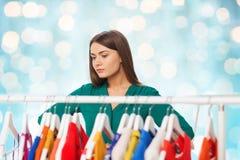 Mujer que elige la ropa en el guardarropa Foto de archivo
