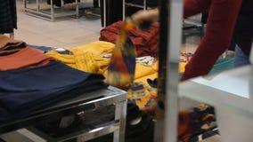 Mujer que elige la ropa en la tienda de ropa metrajes