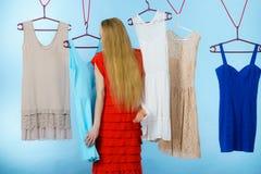 Mujer que elige la ropa en tienda Fotografía de archivo