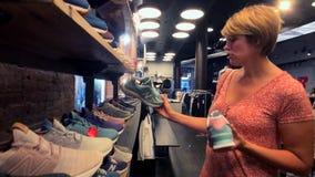 Mujer que elige las zapatillas de deporte de New Balance en la tienda de la compañía en la 5ta avenida almacen de metraje de vídeo