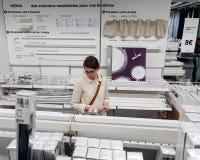 Mujer que elige los accesorios de las cortinas en la tienda de IKEA Imágenes de archivo libres de regalías