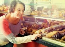 Mujer que elige los pasteles en escaparate del café Fotografía de archivo