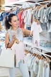 Mujer que elige los pijamas del bebé en boutique de los niños Foto de archivo libre de regalías