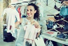 Mujer que elige los pijamas del bebé en boutique de los niños Fotos de archivo libres de regalías
