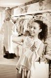 Mujer que elige los pijamas del bebé en boutique de los niños Imagen de archivo