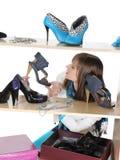 Mujer que elige los zapatos en un almacén Fotos de archivo