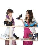 Mujer que elige los zapatos en un almacén Imagenes de archivo