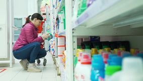 Mujer que elige un detergente en el supermercado almacen de video