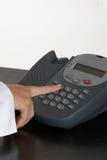 Mujer que empuja el botón del teléfono Imagen de archivo libre de regalías