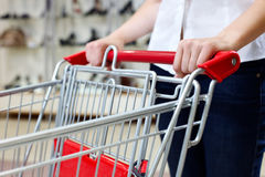 Mujer que empuja el carro de compras imagen de archivo libre de regalías