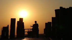 Mujer que empuja la bicicleta sobre el puente de madera en puesta del sol metrajes