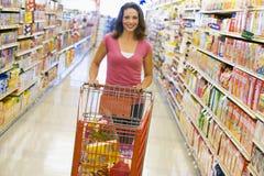 Mujer que empuja la carretilla a lo largo del pasillo del supermercado Imágenes de archivo libres de regalías