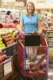 Mujer que empuja la carretilla por el contador de la fruta en supermercado Fotografía de archivo libre de regalías