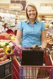 Mujer que empuja la carretilla por el contador de la fruta en supermercado Foto de archivo libre de regalías