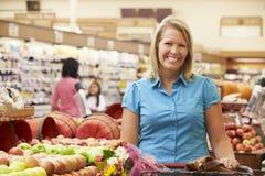 Mujer que empuja la carretilla por el contador de la fruta en supermercado Fotografía de archivo