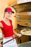 Mujer que empuja la pizza en el horno Imagenes de archivo