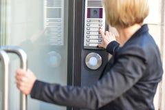 Mujer que empuja un botón del intercomunicador Fotografía de archivo