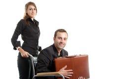 Mujer que empuja a un hombre de negocios lisiado en sillón de ruedas Fotos de archivo
