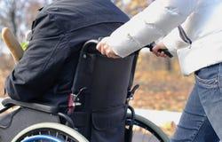 Mujer que empuja a un hombre discapacitado en una silla de ruedas Imágenes de archivo libres de regalías