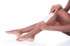 Mujer que encera las piernas contra el fondo blanco fotos de archivo libres de regalías