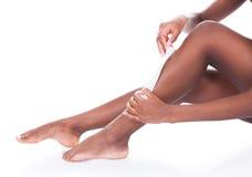 Mujer que encera las piernas contra el fondo blanco foto de archivo