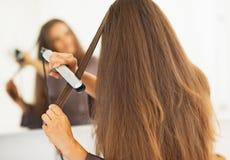 Mujer que endereza el pelo con la enderezadora imagen de archivo libre de regalías