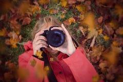 Mujer que enfoca una cámara que pone en hojas de otoño imagenes de archivo