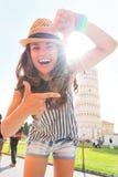 Mujer que enmarca delante de la torre inclinada de Pisa Fotografía de archivo