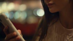 Mujer que enrolla el smartphone, charlando con los amigos en mensajero, tecnologías metrajes