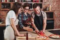 Mujer que enseña sus amigos a cómo cocinar Corte del grupo de personas Imagenes de archivo