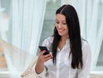 Mujer que envía un mensaje de texto de su teléfono celular Fotografía de archivo libre de regalías
