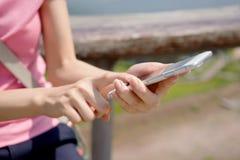 Mujer que envía un texto de su teléfono móvil Fotografía de archivo libre de regalías