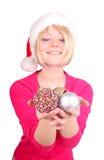 Mujer que envuelve las bolas de la Navidad que desgastan santa ha Foto de archivo