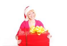 Mujer que envuelve los regalos de Navidad que desgastan santa ha imagenes de archivo