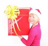 Mujer que envuelve los regalos de Navidad que desgastan santa ha Imagen de archivo