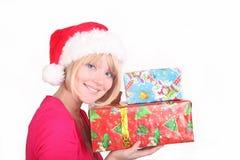 Mujer que envuelve los regalos de Navidad que desgastan santa ha foto de archivo