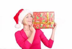 Mujer que envuelve los regalos de Navidad que desgastan santa ha fotografía de archivo libre de regalías