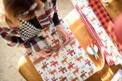 Mujer que envuelve regalos de Navidad en la tabla en el alto ángulo casero imagen de archivo