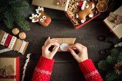 Mujer que envuelve regalos de Navidad modernos con la etiqueta en blanco del regalo en viejo fondo de madera Opinión del pájaro d Foto de archivo libre de regalías