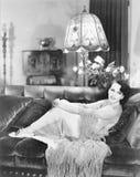 Mujer que envuelve sus manos alrededor de sus rodillas acurrucadas en un sofá (todas las personas representadas no son vivas más  Imágenes de archivo libres de regalías