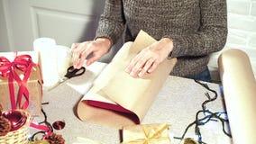 Mujer que envuelve un regalo de la Navidad en casa almacen de metraje de vídeo