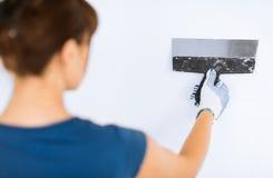 Mujer que enyesa la pared con la paleta fotografía de archivo