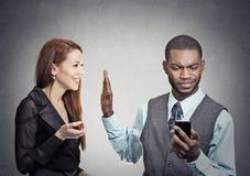 Mujer que es ignorada parada por el hombre hermoso que mira smartphone Imagenes de archivo