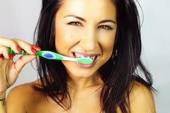 Mujer que es sonrisa cepillada de los dientes Foto de archivo libre de regalías